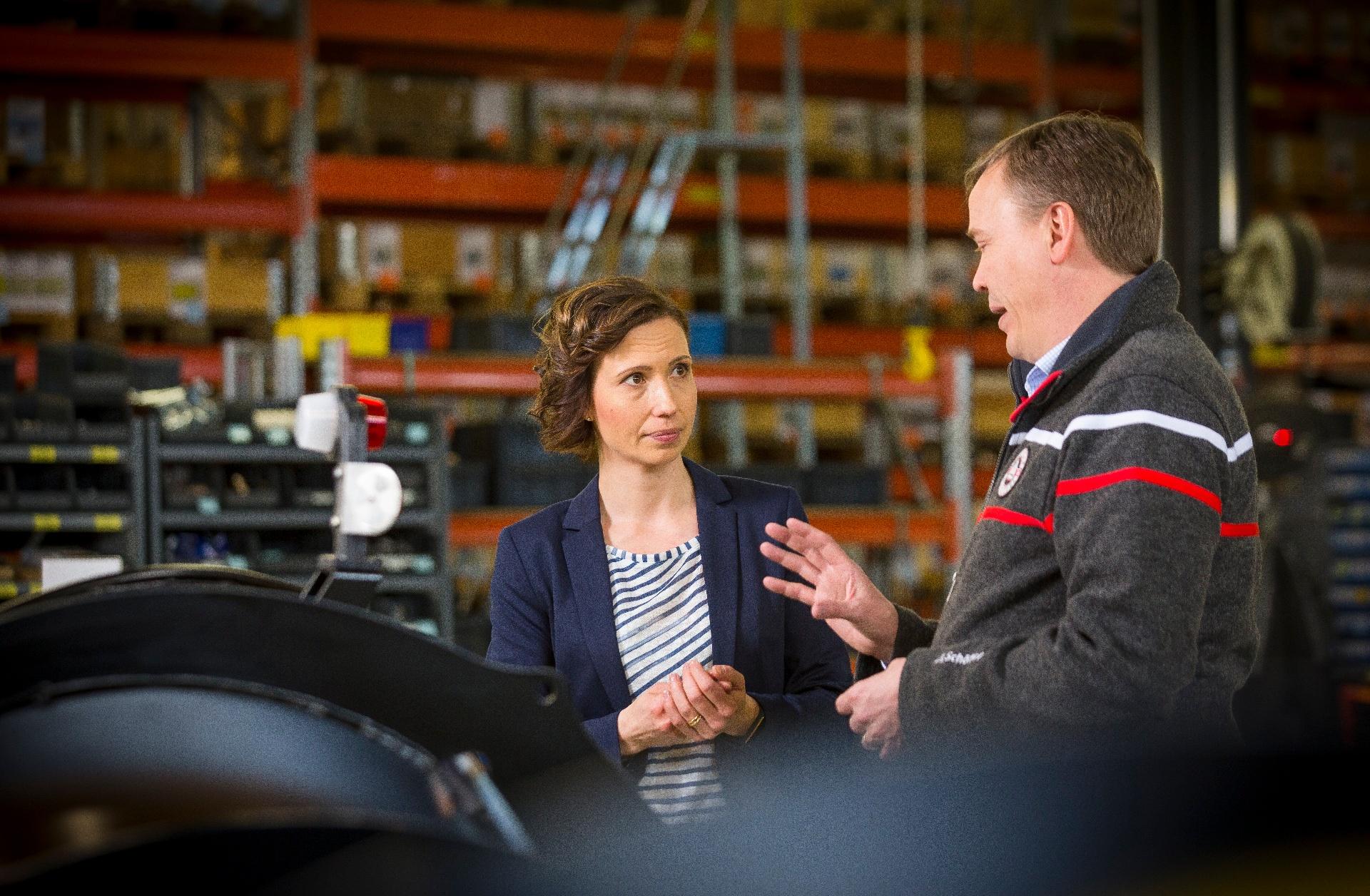 Nainen ja mies keskustelevat teollisuushallissa